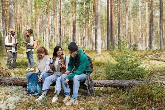 Ganzaufnahme einer verschiedenen gruppe von freunden, die eine pause machen, während sie eine wanderung im wald genießen, konzentrieren sich auf ...