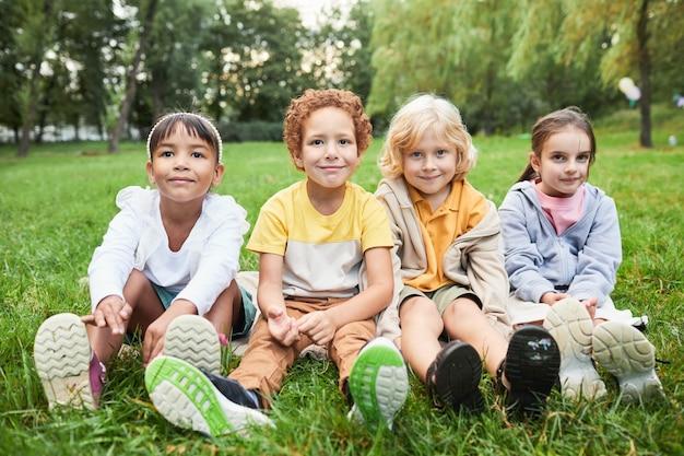 Ganzaufnahme einer verschiedenen gruppe von kindern, die auf gras im park sitzen und in die kamera schauen