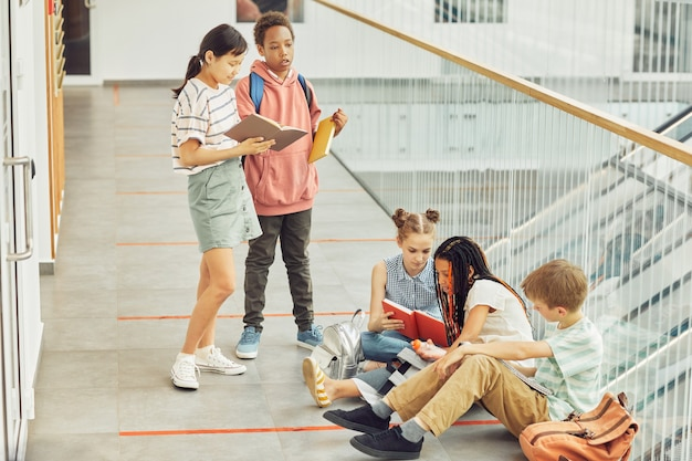 Ganzaufnahme einer verschiedenen gruppe von kindern, die bücher lesen, während sie in der halle der modernen schule warten, kopierraum