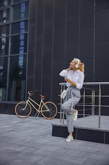 Ganzaufnahme einer wunderschönen modischen dame in grauer hose und weißem hemd, die nach oben schaut, während sie etwas in kopfhörern hört