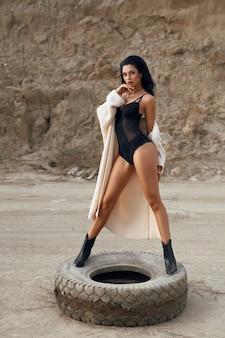 Ganzaufnahme einer zarten jungen frau mit sexy langen beinen, die auf einem alten autoreifen in der wüste steht