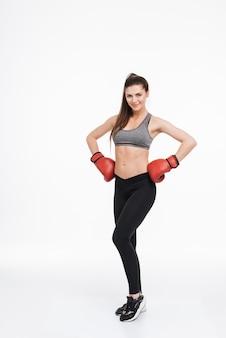 Ganzaufnahme einer zufriedenen lächelnden fitnessfrau, die boxhandschuhe trägt und mit den händen auf den hüften isoliert steht
