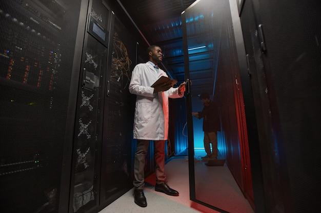 Ganzaufnahme eines afroamerikanischen datenwissenschaftlers, der einen laborkittel trägt, während er mit einem supercomputer im serverraum arbeitet, kopierraum