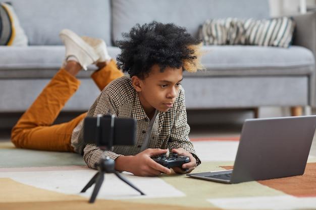 Ganzaufnahme eines afroamerikanischen teenagers, der videospiele spielt, während er zu hause auf dem boden liegt, mit kamerafilmen für online-streaming, kopierraum