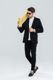 Ganzaufnahme eines ernsten jungen geschäftsmannes mit sonnenbrille, der ein gelbes skateboard auf seinem sholder über grauer wand hält