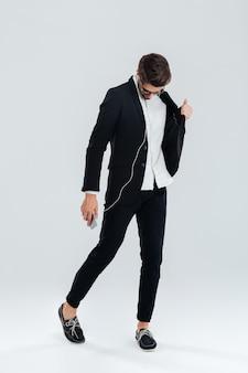Ganzaufnahme eines glücklichen attraktiven jungen geschäftsmannes im schwarzen anzug, der musik mit kopfhörern hört und über graue wand tanzt