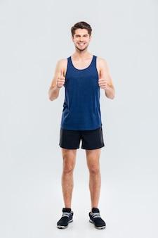Ganzaufnahme eines glücklichen fitness-mannes, der zwei daumen nach oben isoliert auf grauem hintergrund zeigt