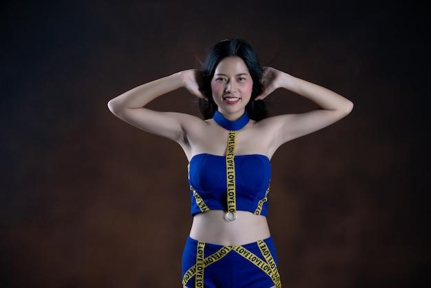 Ganzaufnahme eines glücklichen hübschen mädchens im blauen kleidertanzen