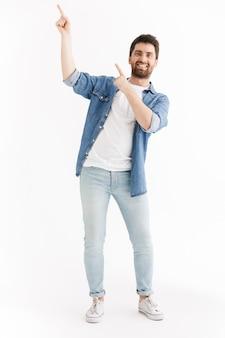 Ganzaufnahme eines gutaussehenden bärtigen mannes in freizeitkleidung, der isoliert steht und auf den kopierraum zeigt