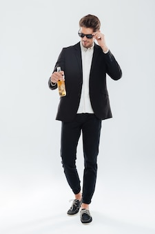 Ganzaufnahme eines gutaussehenden ernsten geschäftsmannes in schwarzer sonnenbrille, der eine bierflasche über grauer wand hält