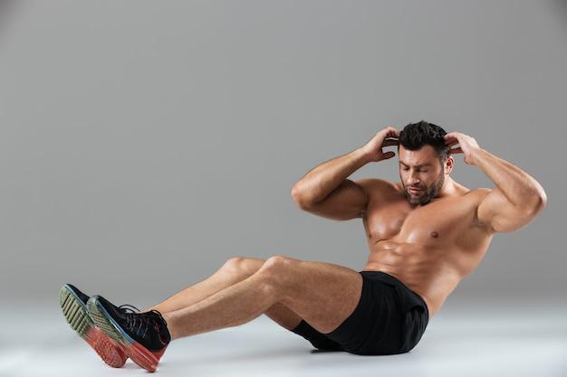 Ganzaufnahme eines hemdlosen männlichen bodybuilders des muskulösen sitzes