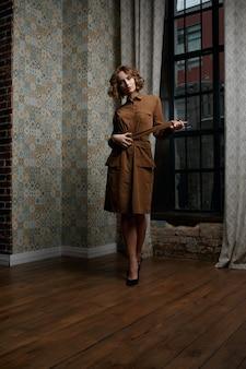 Ganzaufnahme eines herrlichen brünetten mädchens, das ein stilvolles braunes kleid trägt. low-key-aufnahme