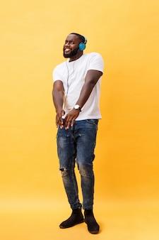 Ganzaufnahme eines jungen afroamerikanischen mannes der kirsche, der musik mit kopfhörern hört