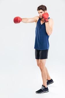 Ganzaufnahme eines jungen gutaussehenden sportlers, der in roten handschuhen auf grauem hintergrund boxt