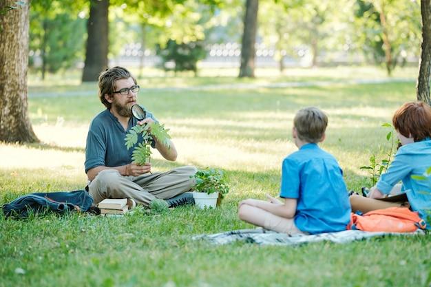 Ganzaufnahme eines lächelnden männlichen lehrers, der mit einem teenager spricht, während er auf grünem gras sitzt und den unterricht im freien genießt