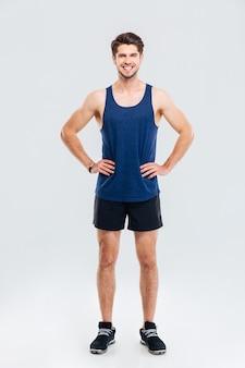 Ganzaufnahme eines lächelnden sportlers, der mit den händen auf den hüften steht, isoliert auf grauem hintergrund