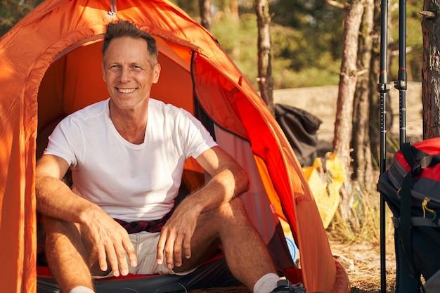 Ganzaufnahme eines lächelnden sportlichen mannes, der auf dem campingplatz sitzt, nachdem er nordic walking in der natur gemacht hat