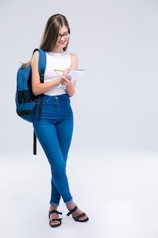 Ganzaufnahme eines lächelnden weiblichen teenagers, der notizen im notizbuch schreibt, isoliert