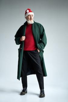 Ganzaufnahme eines modischen mannes mittleren alters mit weihnachtsmütze, der ein stilvolles outfit trägt
