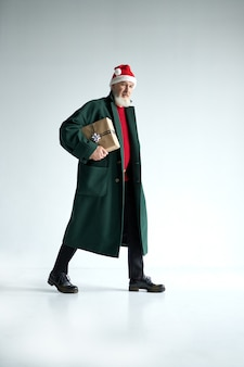 Ganzaufnahme eines modischen reifen mannes mit weihnachtsmütze, der ein stilvolles outfit trägt und anschaut