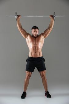 Ganzaufnahme eines muskulösen ernsten hemdlosen männlichen bodybuilders