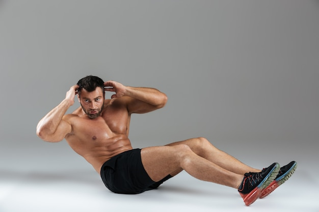 Ganzaufnahme eines muskulösen starken hemdlosen männlichen bodybuilders
