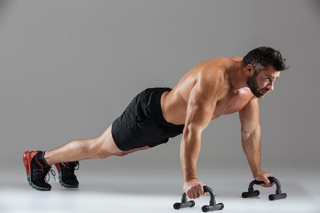 Ganzaufnahme eines starken hemdlosen männlichen bodybuilders des sitzes