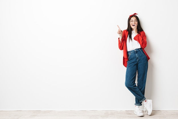 Ganzaufnahme eines süßen aufgeregten teenager-mädchens in lässigem outfit, das isoliert über weißer wand steht und kopienraum präsentiert