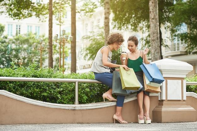 Ganzaufnahme von zwei mädchen, die ihre einkäufe in ihren einkaufstüten vorführen
