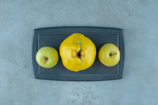 Ganze äpfel und quitten auf einem brett, auf dem marmorhintergrund. foto in hoher qualität
