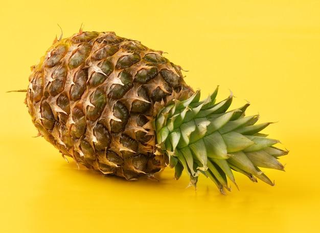 Ganze ananas an gelber wand.