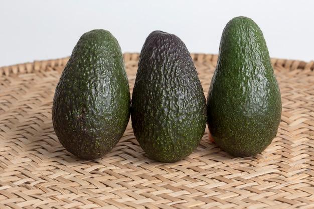 Ganze avocados auf korbsieb
