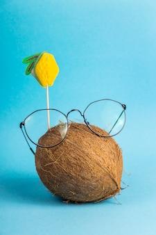 Ganze braune kokosnuss in der schale in stilvollen gläsern mit topper verziert mit früchten