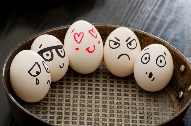 Ganze eier in einer pfanne mit verschiedenen emotionen