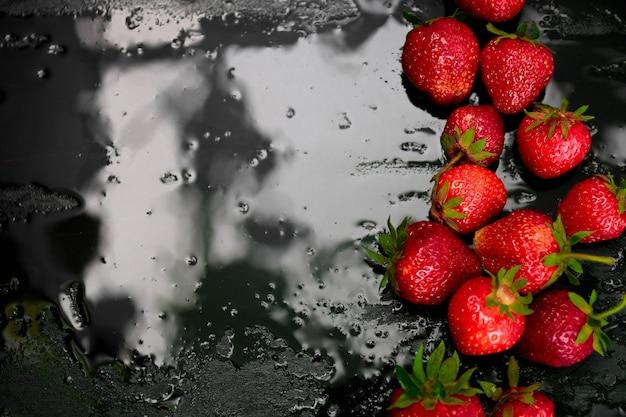 Ganze erdbeeren auf schwarzem hintergrund mit wassertropfen