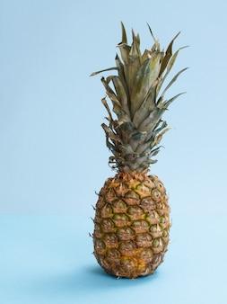 Ganze frische ananas mit blättern auf blauem hintergrund.