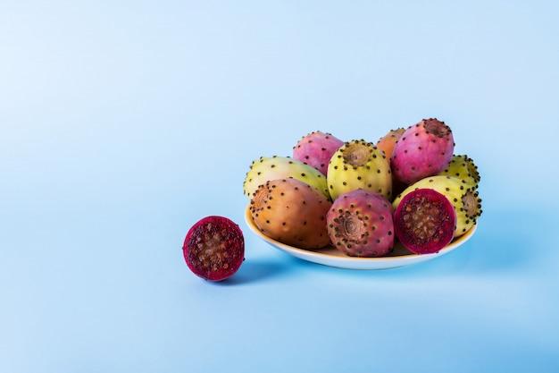 Ganze frische feigenkaktusfrucht in einer platte und schnitt zur hälfte eine opuntie auf einem blauen hintergrundpastellhintergrund.