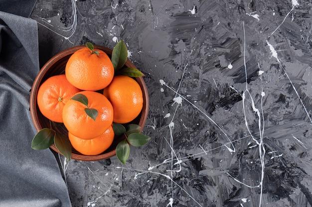 Ganze frische orangenfrüchte mit blättern auf holzschale gelegt