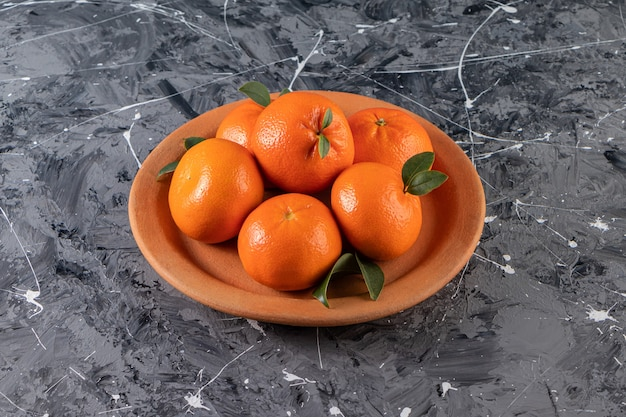 Ganze frische orangenfrüchte mit blättern in tonplatte gelegt