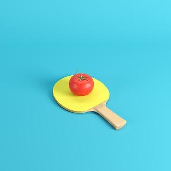 Ganze frische rote tomate mit wasser fällt auf tischtennispaddel mit dem gelben gummi, der auf blauem hintergrund lokalisiert wird