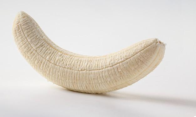 Ganze geschälte banane auf einem weißen hintergrund