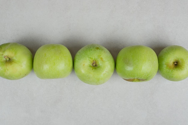 Ganze grüne äpfel auf grauer oberfläche
