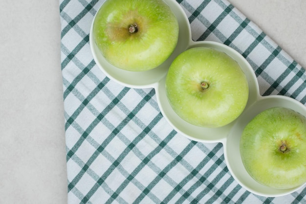 Ganze grüne äpfel auf weißen tellern mit gestreifter tischdecke