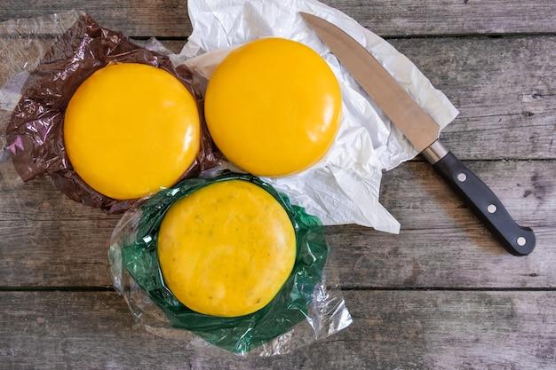 Ganze holland-käse und holländischer ziegenkäse aus den niederlanden auf dem rustikalen holztisch mit messer, draufsicht.