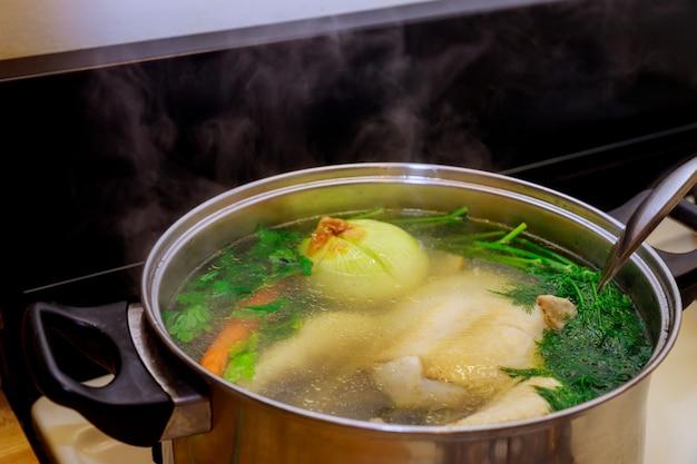 Ganze hühnersuppe mit gemüse in einem topf