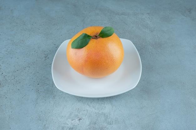 Ganze leckere orange auf einem teller auf dem marmorhintergrund. foto in hoher qualität