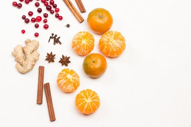 Ganze mandarinen, geschälte mandarinen. preiselbeeren und gewürze, sternanis, zimtstangen auf dem tisch. weißer hintergrund. flach liegen. speicherplatz kopieren