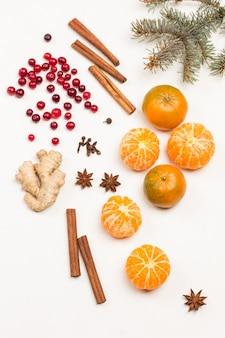 Ganze mandarinen, geschälte mandarinenschnitze. preiselbeeren und gewürze, tannenzweige auf dem tisch. draufsicht