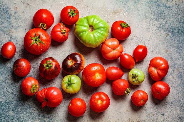 Ganze mehrfarbige reife tomaten auf dunkelblauem hintergrund, draufsicht.