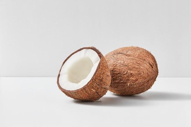 Ganze natürliche exotische reife kokosnussfrucht mit der hälfte auf einem duotone hellgrauen hintergrund mit weichen schatten, kopienraum. vegetarisches konzept.